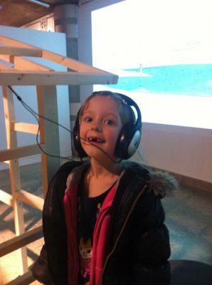 Une fille de 6 ans écoute avec un texte sur les oreilles à la fête du livre de Villeurbanne.