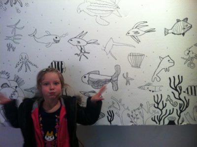 Une fille de 6 ans imite un poissin devant un dessin mural à la fête du livre de Villeurbanne.