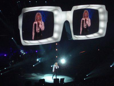 Le chanteur Polnareff en concert avec des lunettes géantentes servant d'écran au dessus de la scène