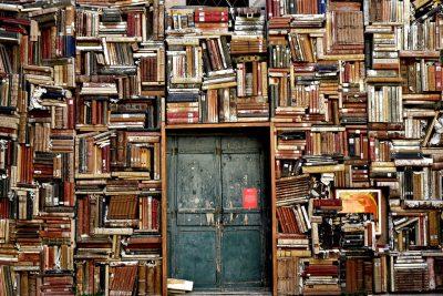 Une bibliothèque surchargée occupant tout un pan de mûr et fermée par une très vieille porte qui semble blindée