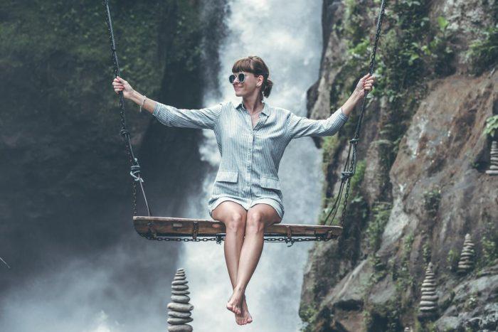 Femme sur une balançoire, avec derrière elle une cascade
